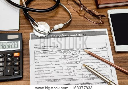 health insurance claim form with stethoscope on clipboard syringe calculator and pen