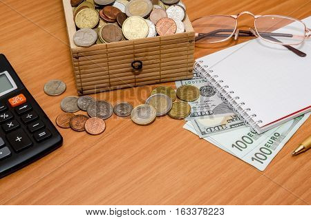open treasure chest with coin. Us dollar and euro with empty notepad glasses and calculator