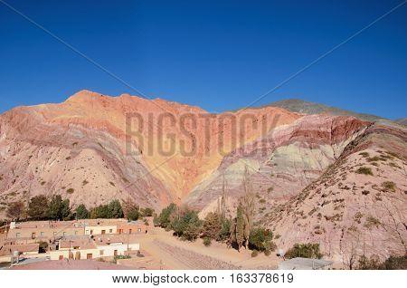 Long shot of the seven color hill or cerro de los siete colores in the village Purmamarca in the canyon quebrada de humahuaca in Jujuy Argentina South America