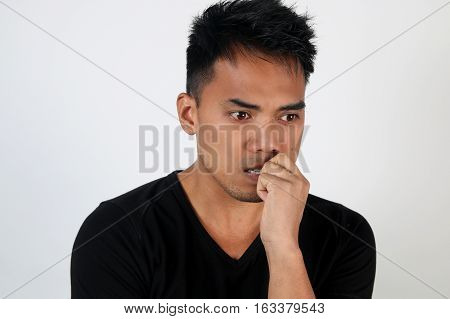 Portrait of a worried young man over a white background