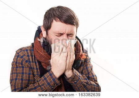 Closeup portrait of sick young man student or worker with allergy or germs cold, blowing his nose with kleenex, looking miserable unwell very sick, isolated on white background. Flu season, vaccine