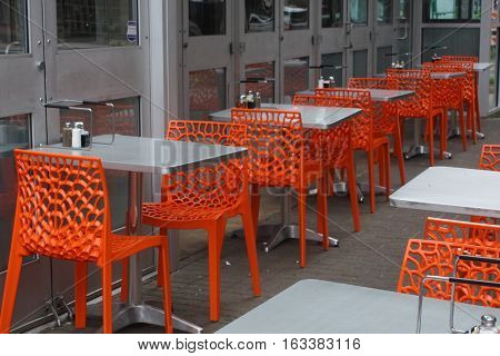 Orange chairs with white tables on sidewalk cafe