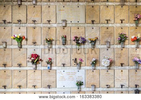 Inscriptions with names and flowers. Hogalidskyrkan, Stockholm, Sweden - September 12, 2015: Inscriptions with names and flowers on memorial wall at a church in Stockholm.  Memorial wall with names.
