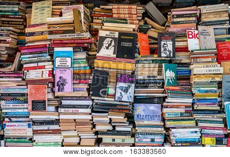 Bookstall with many books. Skopje, Macedonia - September 23, 2016: Bookstall with many different books and titles stacked on each other. Bookstall with stacked books.