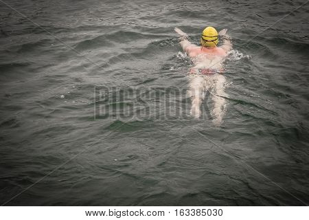 swimmer wear the yellow bathing cap and swim straight to his destination with attempting to win (dark manipulate)