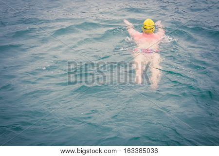 swimmer wear the yellow bathing cap and swim straight to his destination with attempting to win