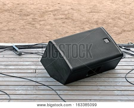 Concert speaker system wires and microphone on the stage with old wooden floor outdoor.