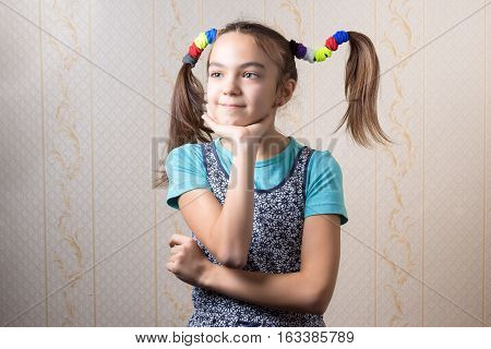 11 year old girl with funny tails thoughtfully propped her chin to the hand