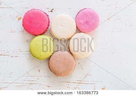 French macaroons on white wood background, top view