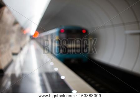 Moving train in subway tunnel, softly blurred