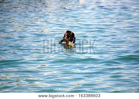HARBOR SPRINGS, MICHIGAN / UNITED STATES - AUGUST 3, 2016: A girl swims at the Zorn Park Public Beach near downtown Harbor Springs.
