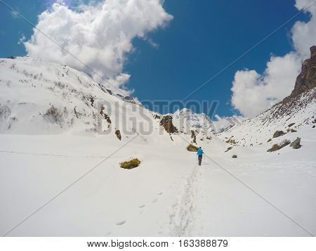 Mountain landscape with snowy peaks and blue sky with fluffy clouds. Trekking path in Sagarmatha National Park. Outdoor sport and travel. Trek to Everest Base Camp. Beautiful winter landscape