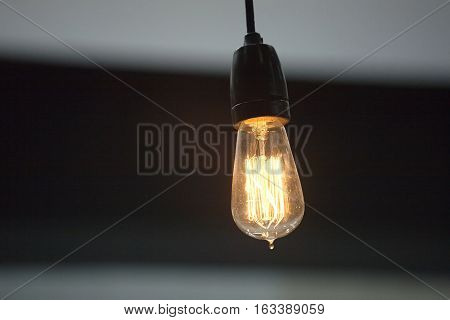 Lighting bulb in lamp-socket lights yellow against dark background closeup
