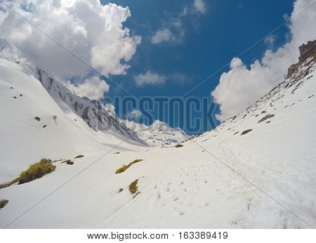 Mountain landscape. Trek to mountain Sagarmatha. National Park in Himalaya. White snow blue sky and rocky peaks. Nepalese severe winter. Nepal eco travel and extreme sport. Beautiful nature