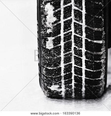 Car tires on winter road. Beautiful winter seasonal background.
