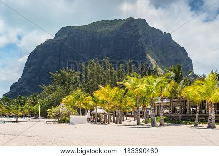 Le Morne Mauritius - December 7 2015: People relax on the Beach at Le Morne Brabant one of the finest beaches in Mauritius. Le Morne Brabant mountain in the background.