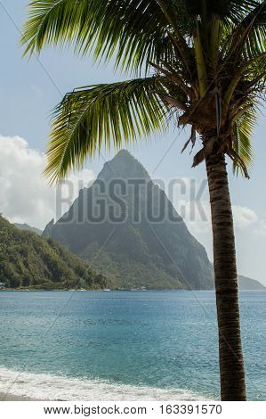 Beach view across the bay at Soufriere to the sea and Piton mountain. Framed with a palm tree