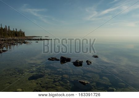 Dead calm afternoon image of clear lake huron water and limestone rocks along shoreline. Clouds reflecting in a zign zag.
