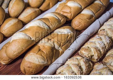 assortment of a baked breads in bakery,  bakery store, bakery shop shelves, baked breads on bakery wood, different baked breads in bakery