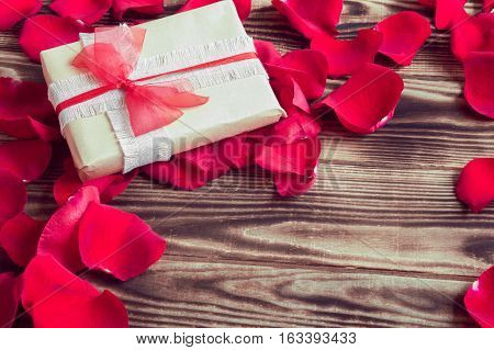 gift around red petals of roses on a wooden brown background