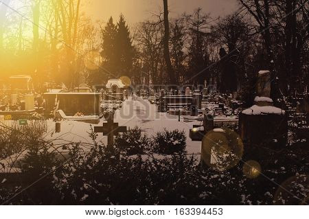 Dark cemetery during the winter with the strong light from setting sun. Dark vintage colors