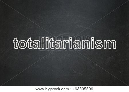 Political concept: text Totalitarianism on Black chalkboard background