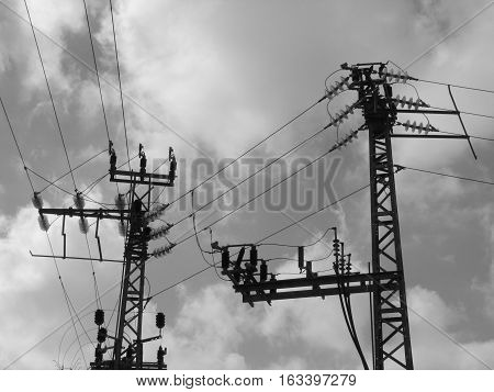 Power line high voltage. Black and white image. Poles obstruct the sky and clouds. Sky and clouds dark. Here you see the dirty water and sky. Industry can be dangerous.