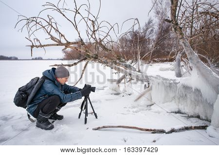 Professional on the lake. Nature photographer takes photos with mirror camera on the river in winter season.