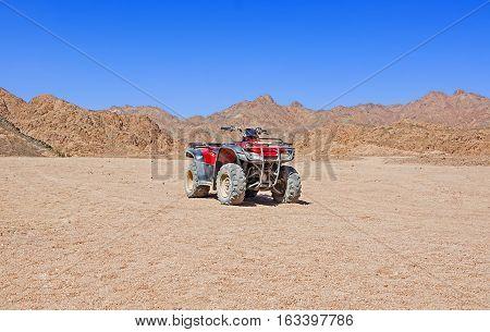 Red quad bike in the desert of Egypt