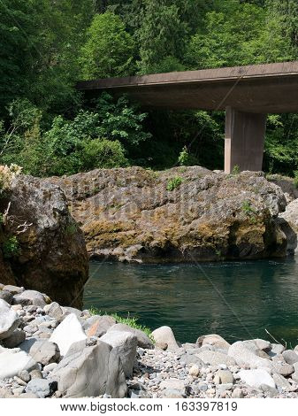 A bridge over the Umpqua River at Swiftwater Recreation Site in Southwestern Oregon on a summer day with a rocky shore including giant boulders.