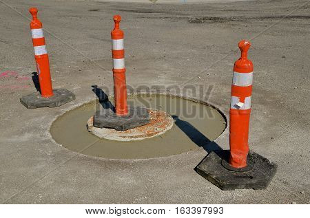 Orange cones surround freshly poured concrete of a sanitary sewer repair project.