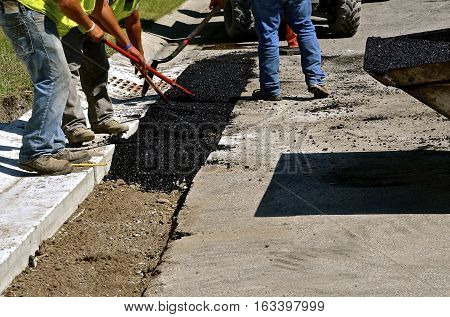 Construction workers spread asphalt with rakes and shovels between the curb and paved road