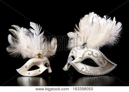 Pretty white venician golden carnival masks with feathers isolated on a mysterious black background