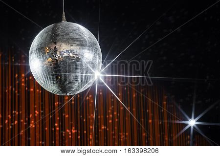 Party disco ball with stars in nightclub with striped orange and black walls lit by spotlight, nightlife entertainment industry