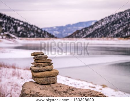 Rock Cairn In Front Of Frozen Lake