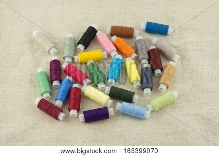 Lot of colored thread spools on beige fabric close up