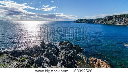 Sun shines bright on the Atlantic Ocean.  View of the cove and the Atlantic from a high cliff in Crow Head, Newfoundland, Canada.