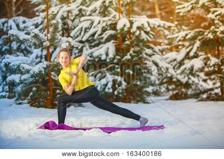 beautiful woman doing yoga outdoors in the snow in yellow T-shirt