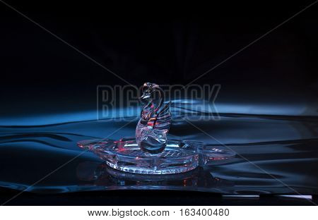 Crystal swan. Crystal swan floating on the water surface photo.
