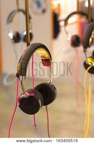 Many color stereo headphones hangs on stand closeup