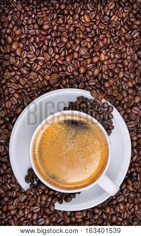 cup of coffee on top of coffee beans