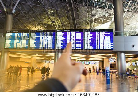 The young man at the international airport indicates finger on flight information board checking your flight