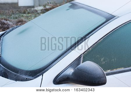 Frozen windshield wiper on car. Frozen windshield. Frozen grey car. Frozen car windshield in winter. Frozen front window of a car. Frozen car windshield in winter. Frozen Front Glass