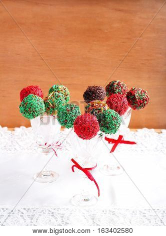 Homemade colorful cakepops in vases over wooden background