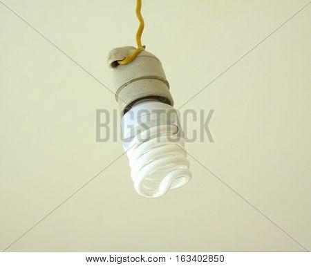 Energy saving bulb in white ceramic cartridge hangs on yellow cord close up