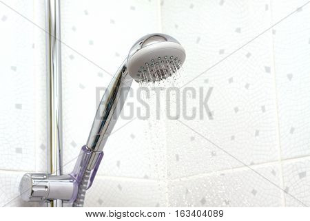 Shower in bathroom with falling water down close up