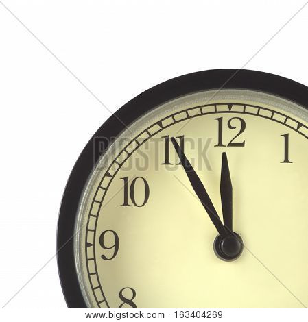 Part of clocks in black case and beige clockface shows 5 minutes to twelve isolated on white close up