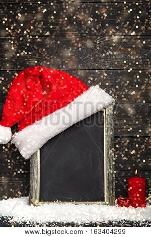 Red Santa hat on the chalkboard with snow and red candle. Frame with copyspace Dreamlike Christmas background