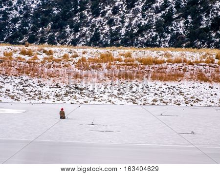 Solitary Ice Fisherman Kneeling On Ice
