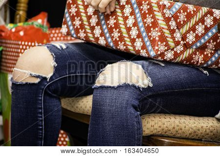 young girl wearing blue jeans with the knees ripped out sitting in chair receiving gift